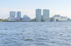 Skyline einer Stadt entlang dem Ufer von einem See bei Sonnenaufgang Lizenzfreie Stockbilder
