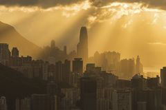 Skyline of Hong Kong city with sun ray under sunset Stock Photos