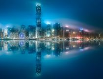 Skyline of Hong Kong in mist from Kowloon, China. Night view and skyline of Hong Kong in mist from Kowloon with reflection on water, China royalty free stock photos