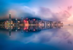 Skyline of Hong Kong in mist from Kowloon, China. Panoramic view and skyline of Hong Kong from Kowloon with reflection on water, China royalty free stock images