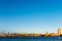 Skyline of midtown Manhattan over Hudson River under blue sky, a stock photo