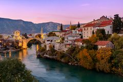 Skyline of Mostar with the Mostar Bridge, Bosnia and Herzegovina. Skyline of Mostar with the Mostar Bridge, houses and minarets, at the sunset in Bosnia and Royalty Free Stock Photos