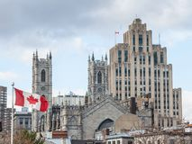 Skyline of Old Montreal, with Notre Dame Basilica in front, a vintage stone Skyscraper in background & a Canadian flag waiving. stock photography