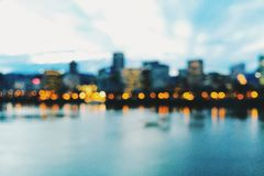 Skyline of Portland, Oregon, at dusk and out of focus. The skyline of Portland, Oregon, as seen from the SE Morrison Bridge. Lights are reflecting into the Stock Image