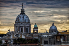 Skyline Rome, domes and monuments. Sunset. Italy. The skyline of the ancient city of Rome. Old Town. Italy. St. Peter and other monuments. Sunset lights Royalty Free Stock Images