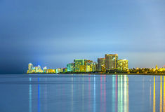 Skyline of Sunny Isles Beach by night with reflections at the surface of the ocean Royalty Free Stock Image
