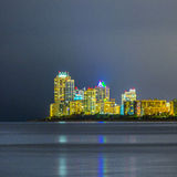 Skyline of Sunny Isles Beach by night with reflections at the surface of the ocean Royalty Free Stock Images