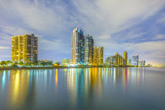 Skyline of Sunny Isles Beach by night with reflections at the surface of the ocean Stock Photos