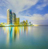 Skyline of Sunny Isles Beach by night with reflections at the surface of the ocean Stock Image