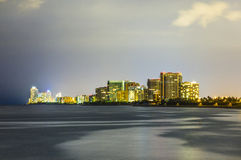 Skyline of Sunny Isles Beach by night with reflections at the surface of the ocean Stock Images