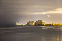 Skyline of Sunny Isles Beach by night with reflections at the surface of the ocean Royalty Free Stock Photos