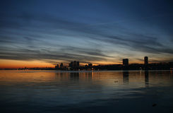 Skyline at sunset. Buildings on water at sunset royalty free stock images