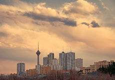 Skyline of Tehran at Sunset with Warm Orange Tone. Milad Tower among high rise skyscrapers in the skyline of Tehran at dusk royalty free stock photo
