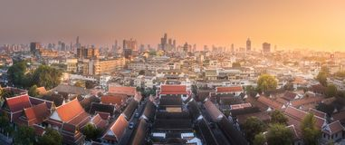 Skyline and temple complex Bangkok. Sunset cityscape with skyscrapers and temple complex of Wat saket or Golden Mountain Bangkok, Thailand Royalty Free Stock Photo