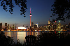 Skyline of Toronto. Toronto, Canada - August 12, 2011: The skyline of Toronto after sunset framed by the silhouette of trees and a Muskoka chair with a view of stock photo