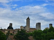 Skyline view of the Italian hill town of San Gimignano in Tuscany. Blue sky and white clouds in the background. stock image