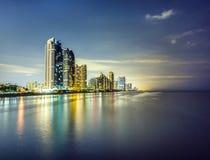 Skyline von Sunny Isles Beach bis zum Nacht mit Reflexionen an der Oberfläche des Ozeans Lizenzfreie Stockfotografie