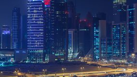 The skyline of the West Bay area from top in Doha timelapse, Qatar. Illuminated modern skyscrapers aerial view from rooftop at night. Traffic on the road stock video