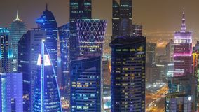 The skyline of the West Bay area from top in Doha timelapse, Qatar. Illuminated modern skyscrapers aerial view from rooftop at night. Traffic on the road stock video footage