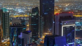 The skyline of the West Bay area from top in Doha timelapse, Qatar. Illuminated modern skyscrapers aerial view from rooftop at night. Traffic on the road stock footage