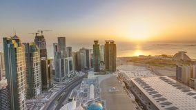 The skyline of West Bay and Doha City Center during sunrise timelapse, Qatar. Modern skyscrapers and traffic on the road. Gulf on background stock video