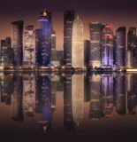 The skyline of West Bay and Doha City, Qatar. The skyline of West Bay and Doha City Center at night with reflection on water, Qatar. Clipping path of sky royalty free stock photos