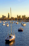 Skyline with yachts. Yachts in the foreground with a beautiful sunrise glow on the skyline of buildings in background Stock Images