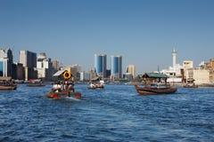 Skylineansicht von Dubai Creek mit traditionellem Boot Stockfotografie