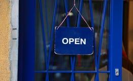 Skylt av öppningen av den blåa dörren Fotografering för Bildbyråer