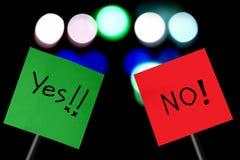 Skylt med ordet ja på dokument med olika förslag och inte på rött papper Fotografering för Bildbyråer