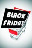 Skylt med textsvarten fredag i en shoppingvagn Royaltyfri Foto