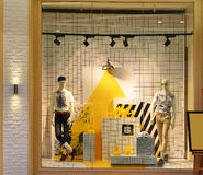 Skyltdockor i mode shoppar fönstret som tänds av lett ljus Arkivbild