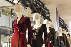 Skyltdockor som står i den tillfälliga kvinnan för shoppafönsterskärm, klumpar ihop royaltyfri fotografi