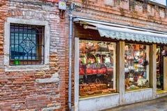 Skyltfönstret av italiensk detaljhandel för tegelstenväggen shoppar sälja påsar i Venedig, Italien royaltyfria foton