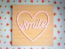 Skyltleende inom en rosa hjärta med träramen och bakgrund med rosa blommor royaltyfria foton