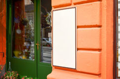 Skyltsikten av den tomma vita modellsignagen i ram med apelsinen shoppar väggen i bakgrund Royaltyfri Bild