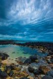 Skymning över vulkanisk rockpöl för hav på en molnig sky Arkivfoto