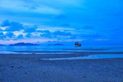 Skymning för blå himmel för fartygsolnedgång röd på stranden Arkivbild