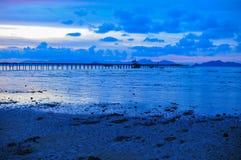 Skymning för blå himmel för fartygsolnedgång röd på stranden Royaltyfri Bild