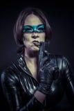Skymning iklädd svart latex för farlig kvinna som beväpnas med vapnet Arkivbild