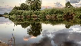 Skymning på flodbanken Det finns många moln i himlen Lopp och rekreation i natur Arkivbild