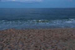 Skymning på havet med den sandiga stranden med fotspår royaltyfri bild