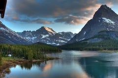 Skymning på Swiftcurrent sjön, glaciärnationalpark, Montana, USA royaltyfria bilder