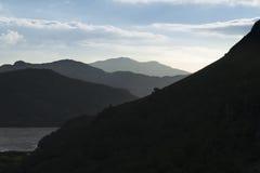 Skymning skuggade gråa berg, Silhouetted, det Nant Gwynant passerandet arkivfoto