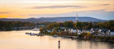 Skymningnedgångar över staden och floden som riverboats av turister tycker om aftonen royaltyfri fotografi