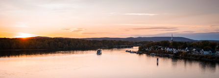 Skymningnedgångar över staden och floden som riverboats av turister tycker om aftonen royaltyfri foto