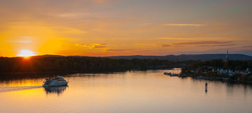 Skymningnedgångar över staden och floden som riverboats av turister tycker om aftonen fotografering för bildbyråer