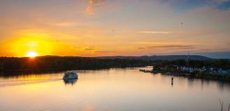 Skymningnedgångar över staden och floden som riverboats av turister tycker om aftonen royaltyfria bilder