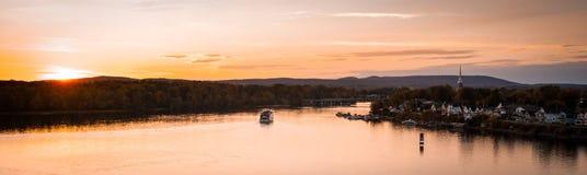 Skymningnedgångar över staden och floden som riverboats av turister tycker om aftonen royaltyfri bild