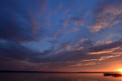 Skymningsolnedgång i himlen över sjön arkivfoto